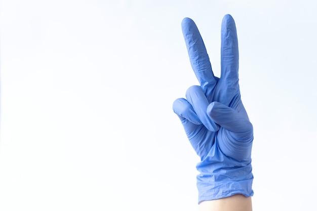 ピンクの背景に医療用手袋をはめた手手袋を着用するプロセス