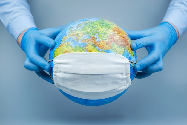 의료 장갑에 손을 지구에 보호 마스크를 넣어. 세계 코로나 바이러스 / 코로나 바이러스 공격 개념 바이러스와의 싸움의 개념입니다.