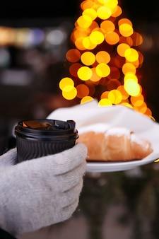 Руки в варежках держат чашку горячего кофе и круассан