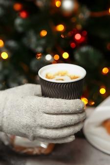 장갑을 낀 손은 뜨거운 커피를 들고 있습니다. 겨울에 갈 커피.