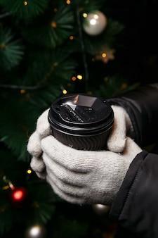 장갑을 낀 손은 뜨거운 커피를 들고 있습니다. 겨울에 갈 커피