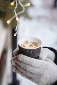 Руки в варежках держат чашку горячего кофе. кофе с собой зимой.