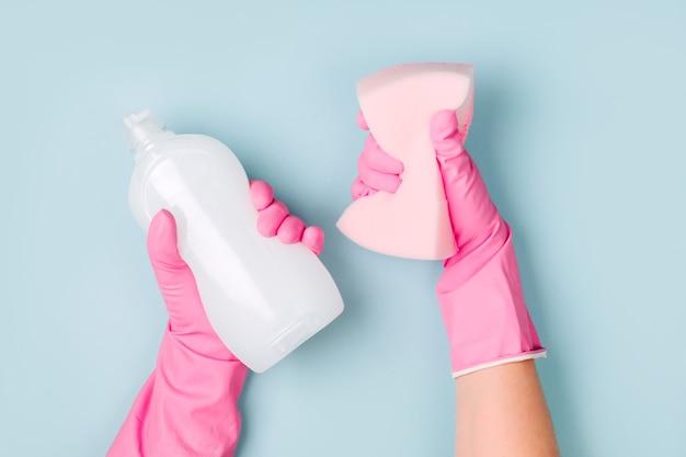 ピンクの手袋をはめた手は、洗剤とクリーニングアクセサリーを持っています。クリーニングまたはハウスキーピングの概念の背景。スペースをコピーします。フラットレイ、上面図。