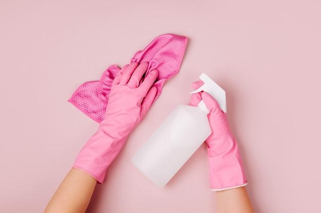 ピンクの手袋をはめた手は、洗剤とクリーニングアクセサリーを保持しますクリーニングまたはハウスキーピングの概念
