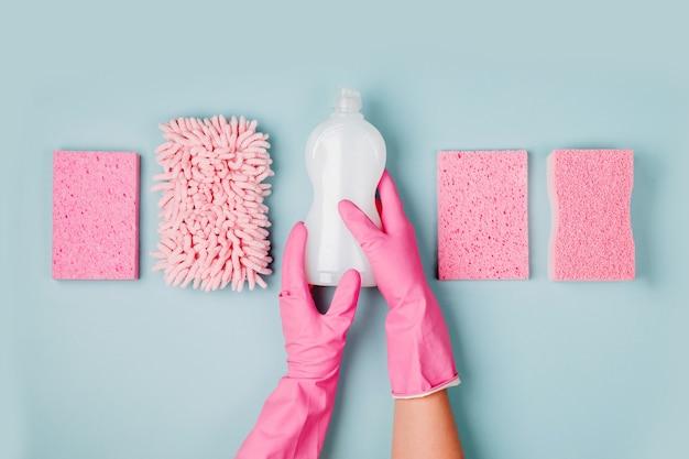 ピンクの手袋をはめた手は、洗剤とクリーニングアクセサリーを持っていますクリーニングまたはハウスキーピング