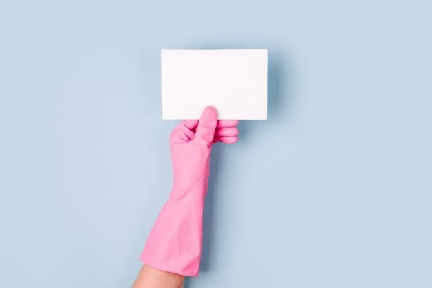 ピンクの手袋の手は空のカードを保持します。クリーニングまたはハウスキーピングの概念の背景。スペースをコピーします。フラットレイ、上面図。