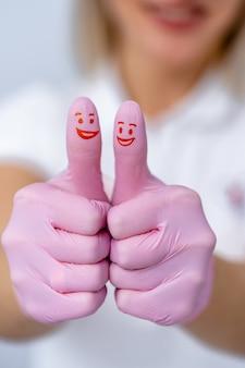 Руки в розовых перчатках перед камерой. показываю крутой знак. нарисовал красные улыбки на больших пальцах.