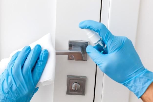 보호 장갑을 낀 손 - 하나는 분무기를 소독제로, 다른 하나는 소독액을 적신 천으로 문 손잡이를 닦습니다.