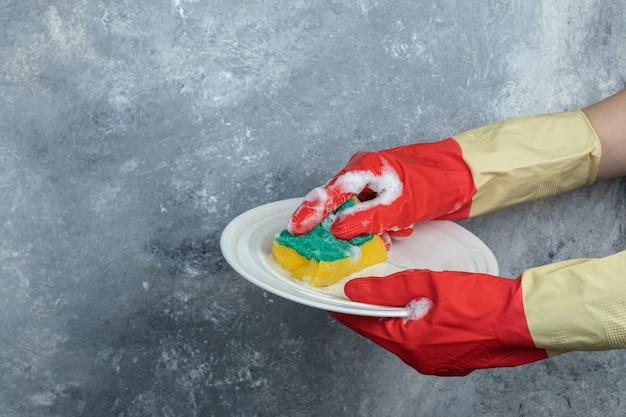 스폰지로 접시를 세척하는 보호 장갑에 손을.