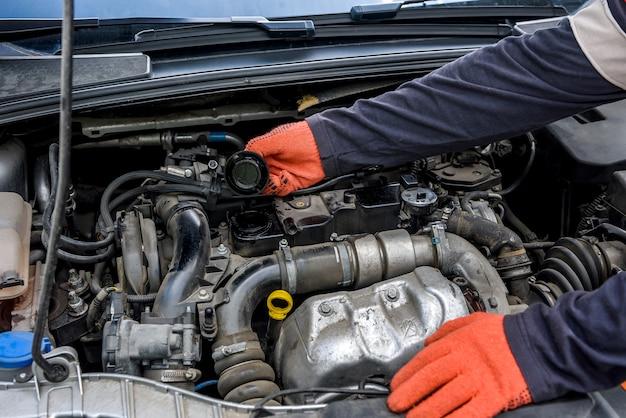 자동차 엔진 보호 장갑에 손을 닫습니다. 자동차 수리 개념