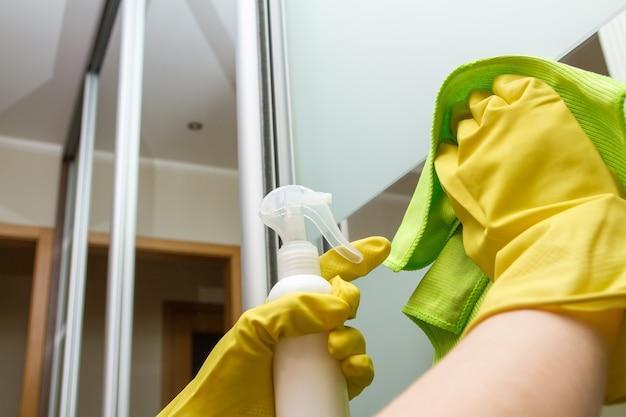 걸레와 스프레이가 있는 보호 장갑을 낀 손이 유리 옷장을 청소하고 있습니다