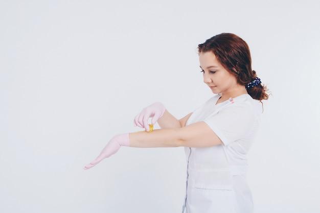 ゴム手袋のクローズアップの手。医師はワックス、蜂蜜を入れます。メディックは脱毛の準備をしています。医学、医療機器、医療、美容業界、脱毛、天然素材の概念