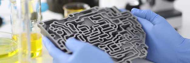 Руки в резиновых перчатках держат автоматическую коробку передач в химической лаборатории крупным планом