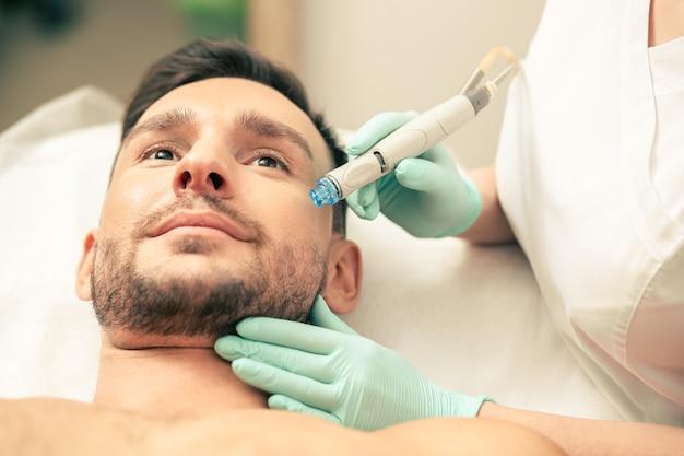 Руки в резиновых перчатках держат современное устройство возле лица спокойного человека во время процедуры увлажнения кожи