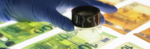 지폐 근접 촬영으로 돋보기를 들고 고무 장갑에 손. 위조 돈 개념