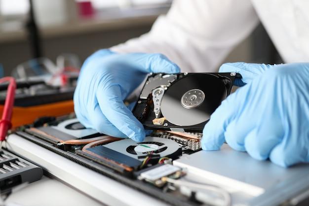 Руки в резиновых перчатках, ремонтирующих крупный план электронного ноутбука. диагностика и ремонт компьютеров