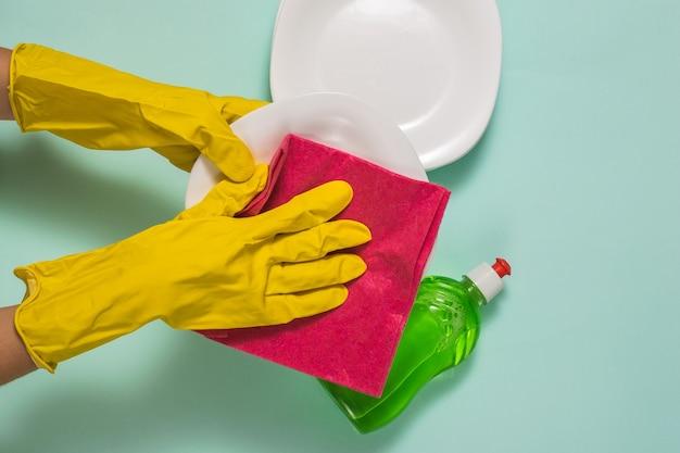 고무 장갑을 낀 손은 빨간 천으로 깨끗한 접시를 닦습니다.