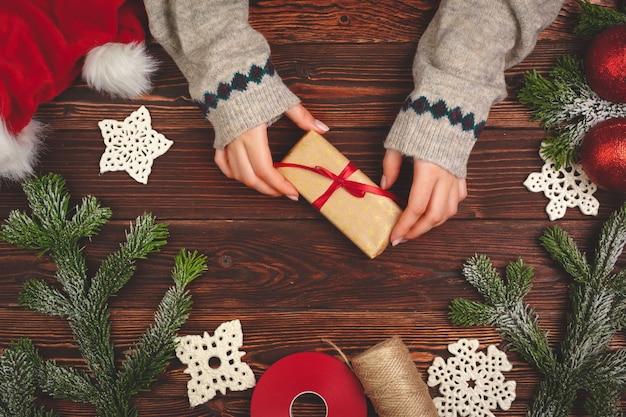 Руки в свитере, держа подарок на деревянном столе с рождественскими украшениями