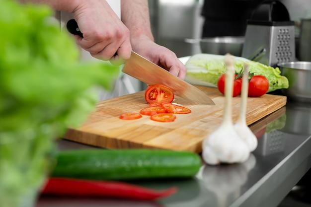 キッチンでサラダ用の新鮮な野菜を切る手
