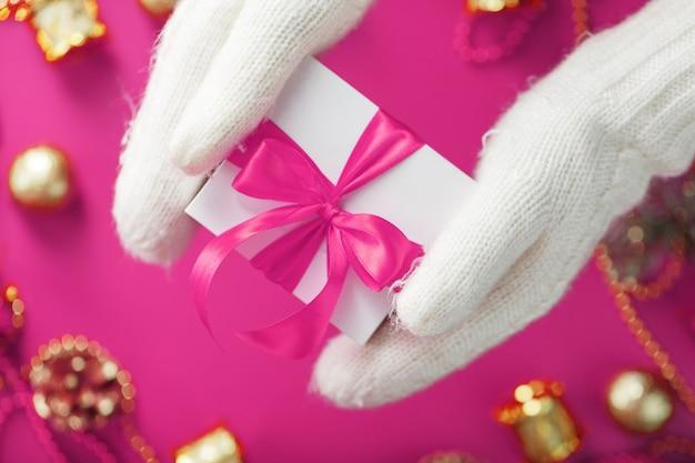 Руки в теплых белых вязаных рукавицах держат белую подарочную коробку с розовым бантом на розовом фоне.