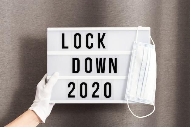 흰 장갑을 낀 손은 메시지 잠금 2020과 수술 용 보호 마스크가있는 라이트 박스를 들고 있습니다.