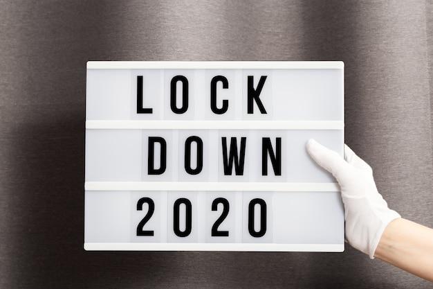 흰 장갑을 낀 손은 메시지 잠금 2020이있는 라이트 박스를 들고 있습니다. 2020 년 올해의 단어는 잠금입니다.
