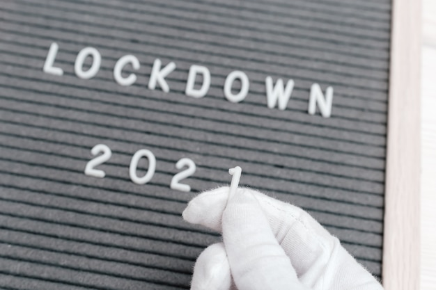 흰 장갑을 낀 손은 번호 1을 잡고 메시지 텍스트 잠금 2020에서 번호 0을 번호 1로 바꿉니다.
