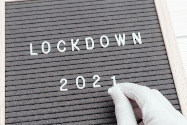 흰 장갑을 낀 손은 숫자 1을 잡고 메시지 텍스트 잠금 2020에서 숫자 0을 숫자 1로 바꿉니다.