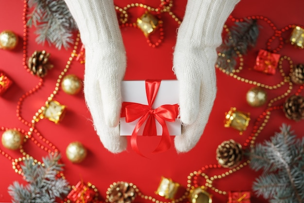 Руки в белых вязаных рукавицах, держа подарок на красном фоне. белая коробка с красной лентой. устойчивый праздничный образ жизни. рождественские украшения