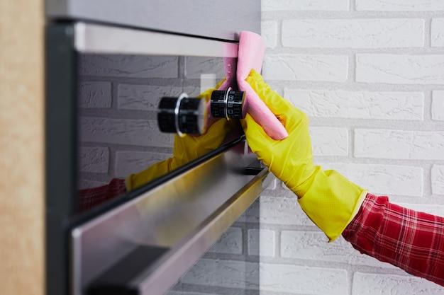 キッチンのピンクのぼろきれでオーブンパネルを掃除する黄色い手袋の手。クローズアップ。