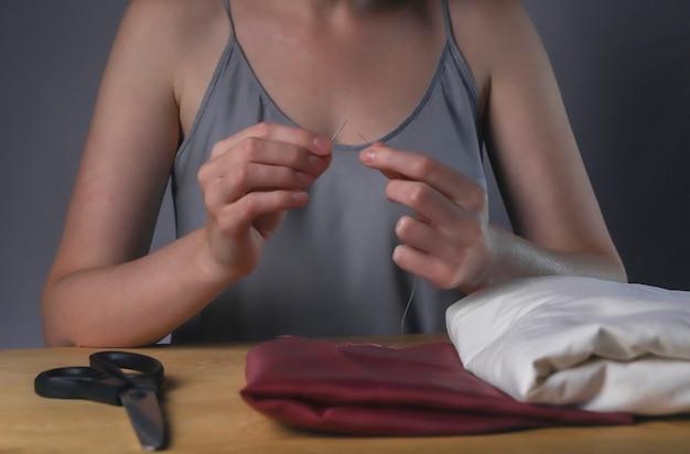 Руки заправляют нить в игольное отверстие для шитья за деревянным столом.