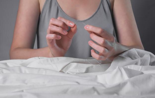Руки заправляют нить через игольное отверстие для шитья. концепция концентрации и внимания.