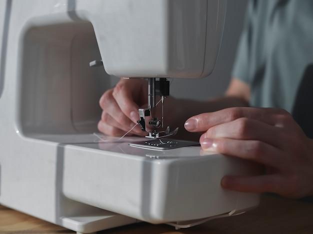 Руки заправляют нить через игольное отверстие в швейной машине.