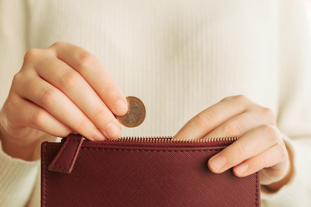 Hands introducing a coin in a wallet