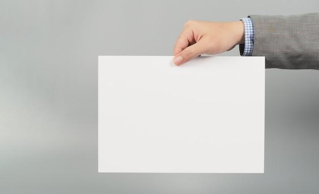 Руки держит доску белую бумагу на сером фоне. носите серый костюм. концепция бизнесмена.