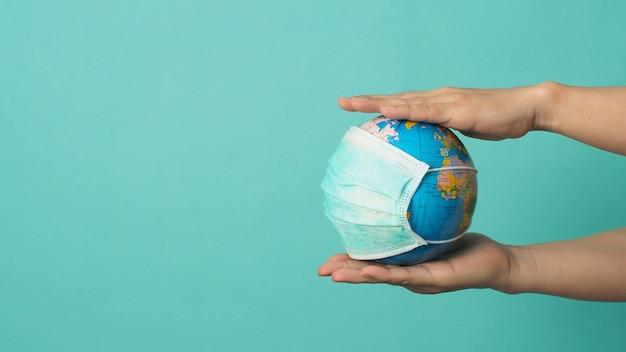 Руки держат земной шар и маску для лица на мятно-зеленом или синем фоне тиффани. концепция covid-19.