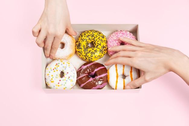 手はドーナツボックスに色付きの艶をかけられたドーナツを取っています。手はさまざまなフレーバーのドーナツをつかんでいます。オフィスや休憩所での不健康なおやつ。スペースをコピーし、モックアップします