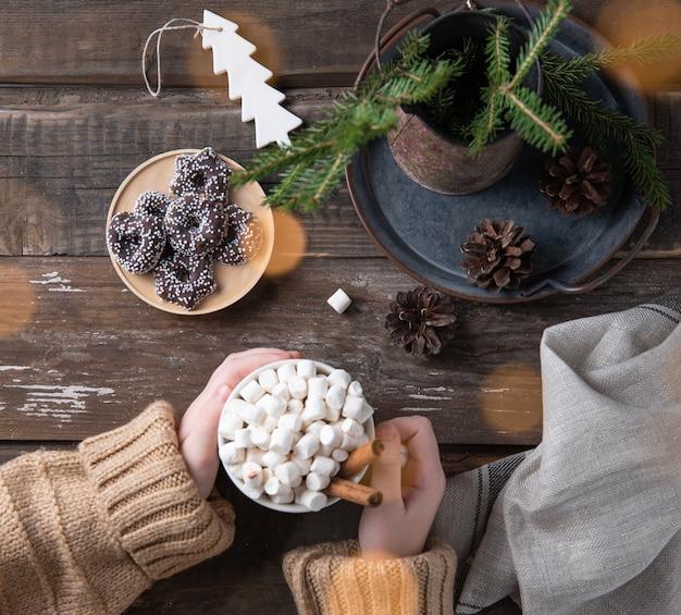 손은 보케, 쿠키, 콘, 전나무가 있는 오래된 갈색 나무 테이블에 계피와 함께 카카오와 마시멜로의 크리스마스 머그를 보관합니다. 새해 분위기. 평면도