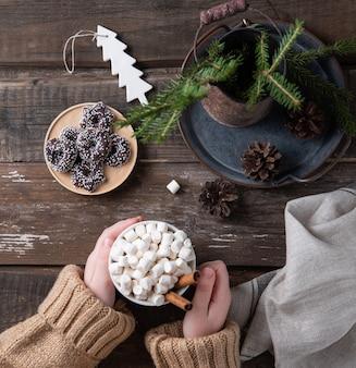 手は、クッキー、コーン、モミの入った古い茶色の木製テーブルに、シナモンと一緒にカカオとマシュマロのクリスマスマグカップを置きます。新年の気分。上面図