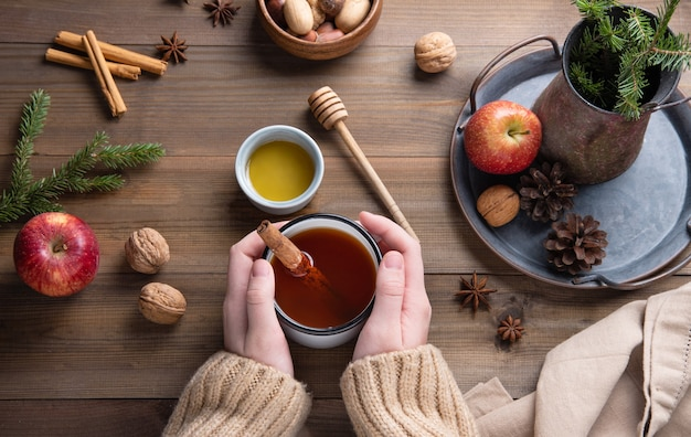 Hands keep  mug of  aroma  christmas apple tea with cinnamon on a wooden table. top view