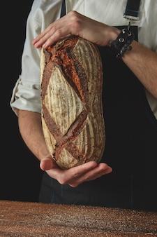 手は黒い背景に暗いエプロンと木製のテーブルの焼きたてのパンを保持します