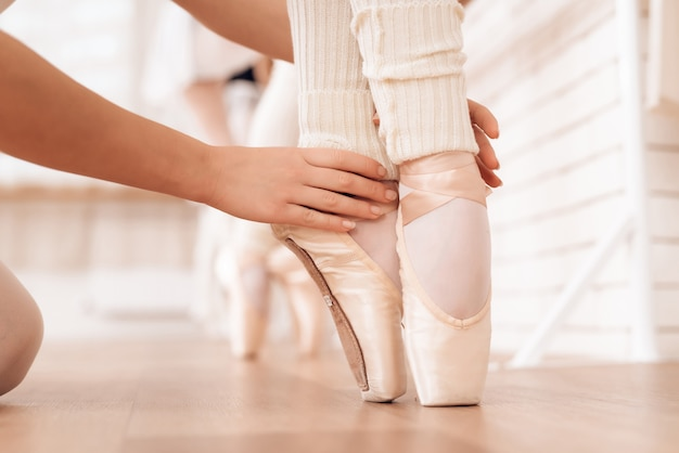 Hands of kid legs of ballerina in pointe shoes.