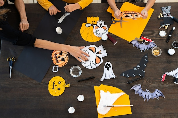 Hands of kids and young woman making halloween paper symbols