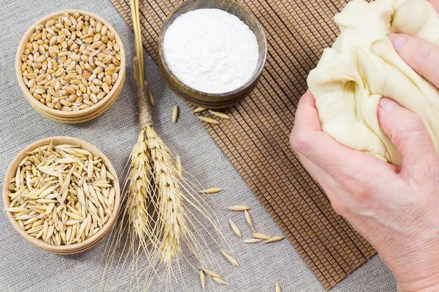手で生地をこねます。小麦、オート麦、小麦粉を木箱に入れたもの。小枝小麦