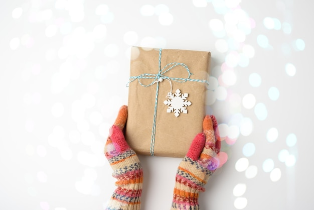 Hands in knitted mittens hold a box in brown paper and tied with a rope on a white background with bokeh, top view