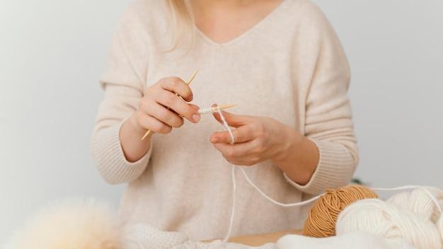 Mani che lavorano a maglia con il primo piano del filo bianco