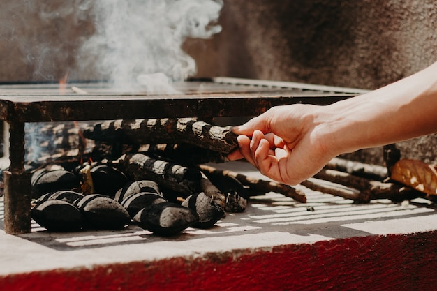 Hands lighting wood and charcoal for a grill.