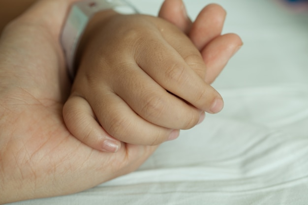 Hands of littel boy and hands of mother, wristband barcode in hospital bed