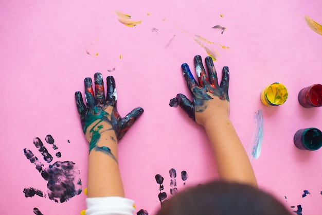 Hands of a little boy painting with watercolors on pink paper sheet.