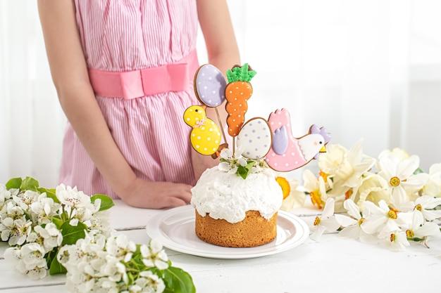 Le mani di una bambina che decora una torta festiva. il concetto di preparazione per le vacanze di pasqua.